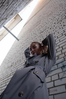 Modèle asiatique attrayant en trench-coat debout près du mur tourné depuis le point inférieur
