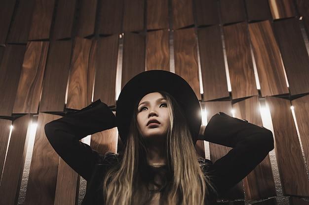 Modèle asiatique à la mode en chapeau posant sur un mur élégant