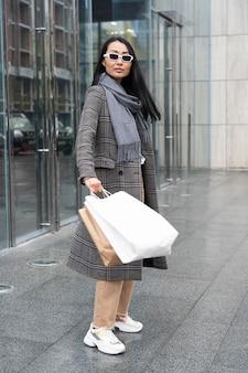 Modèle asiatique de tir complet tenant des sacs