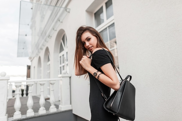 Modèle assez belle jeune femme dans une élégante robe noire avec un élégant sac à dos en cuir noir se déplace dans la ville. jolie fille à la mode bénéficie d'une promenade dans une rue. style de jeunesse de rue.