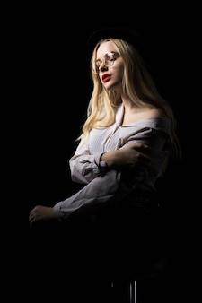 Modèle assez blonde à lunettes portant un chemisier aux épaules nues, posant avec une lumière de studio dramatique