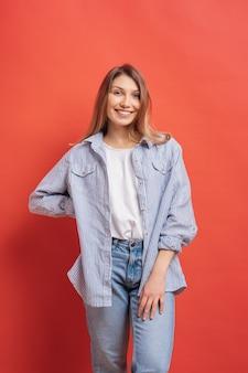 Modèle assez féminin posant avec une expression de visage souriant sur mur rouge