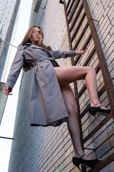 Modèle attrayant asiatique portant un trench-coat debout sur une échelle d'incendie sur le mur