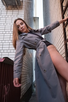 Modèle attrayant asiatique portant un trench-coat escalade échelle sur mur à l'extérieur