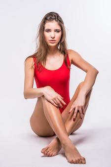 Modèle attrayant aux cheveux brune est assis sur le sol habillé en maillot de bain rouge isolé sur fond blanc