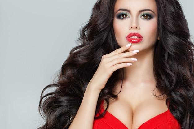 Modèle attrayant avec des cheveux bouclés foncés, des lèvres rouges, du maquillage et un soutien-gorge rouge, une femme brune avec une coiffure parfaite
