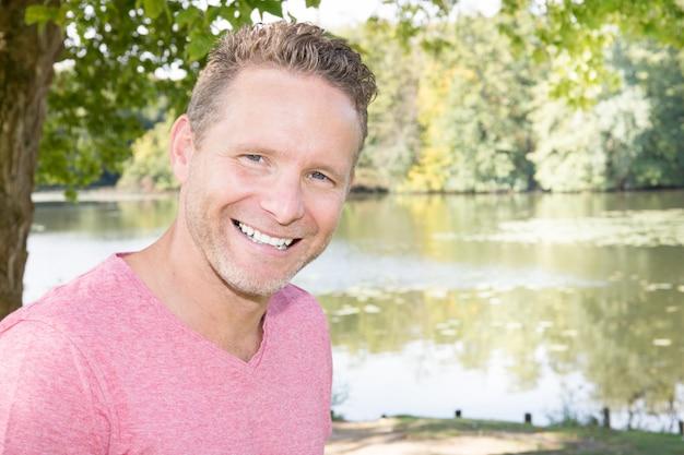 Modèle attrayant homme adulte posant au lac de la rivière
