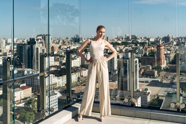 Modèle attrayant en vêtements décontractés posant magnifiquement sur le toit de la maison sur fond de ville. fille sur la terrasse d'été