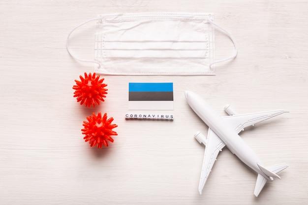 Modèle d'avion et masque facial et drapeau estonie. pandémie de coronavirus. interdiction de vol et fermeture des frontières pour les touristes et les voyageurs atteints de coronavirus covid-19 d'europe et d'asie.