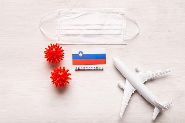 Modèle d'avion et masque facial et drapeau slovénie. pandémie de coronavirus. interdiction de vol et fermeture des frontières pour les touristes et les voyageurs atteints de coronavirus covid-19 d'europe et d'asie.