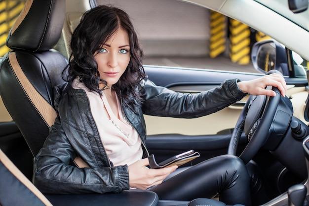 Modèle de belle femme assise dans la voiture avec le téléphone à la main et en tapant un message