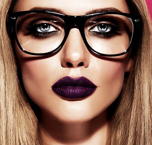 Modèle de belle femme blonde chaude avec un maquillage quotidien frais avec des lèvres violet foncé et une peau saine et propre dans des verres
