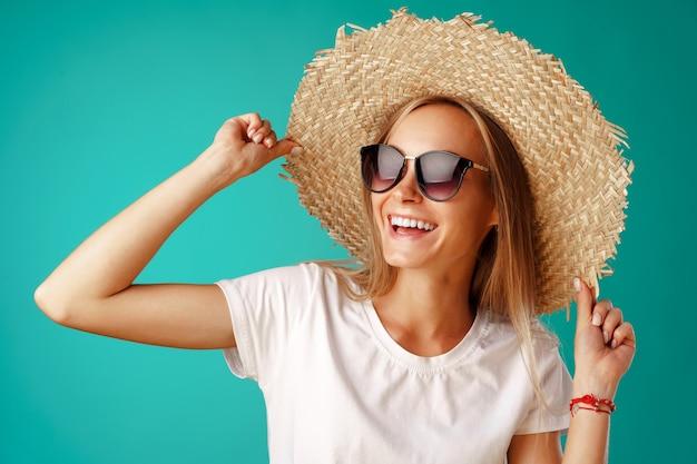 Modèle de belle femme blonde posant dans un chapeau de paille.