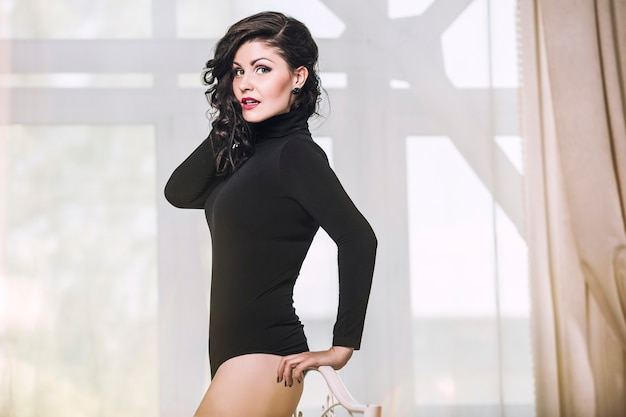 Modèle de belle femme brune dans une lingerie body noir dans la chambre contre la fenêtre