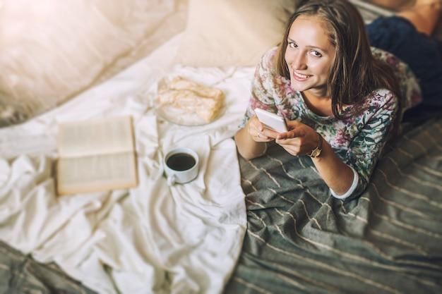 Modèle De Belle Femme Avec Café, Pâtisseries, Téléphone à La Maison Sur La Couverture. Petit Déjeuner, Matin, Maison, Confort Photo Premium