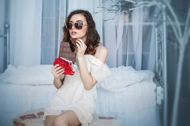 Modèle de belle femme avec des carreaux de chocolat noir dans les mains contre l'intérieur de la chambre