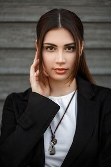 Modèle de belle femme élégante dans un manteau noir dans la rue