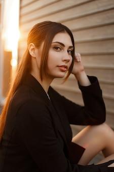 Modèle de belle femme élégante dans un manteau noir de mode au coucher du soleil
