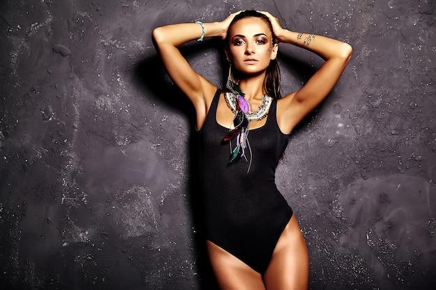 Modèle belle femme en lingerie noire d'été avec maquillage créatif lumineux posant près du mur gris