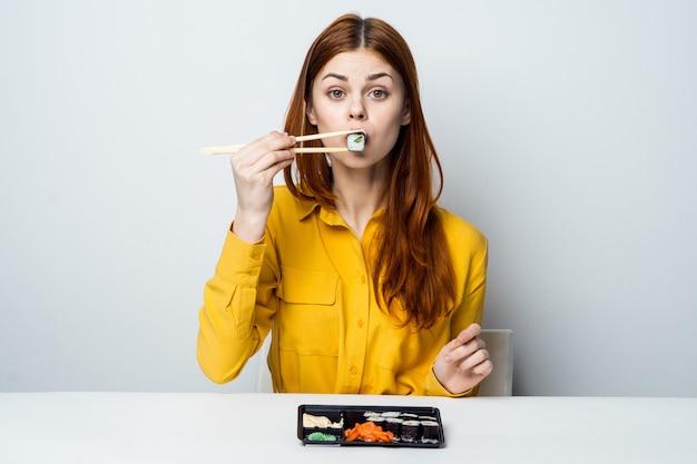 Modèle belle femme mangeant des sushis et des rouleaux de livraison de nourriture à la table dans une chemise jaune posant différentes émotions