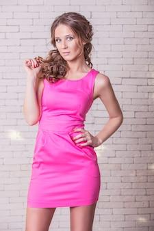 Modèle de belle femme en robe courte rose contre un mur de briques blanches