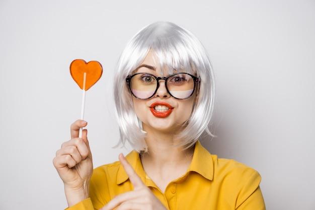 Modèle de belle femme avec une sucette coeur à la table dans une chemise jaune pose des émotions différentes. la saint-valentin