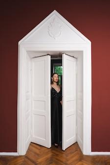 Modèle de belle femme vêtue d'une élégante longue robe noire dans une pose de mode dans un intérieur moderne avec porte blanche sur mur bordeaux