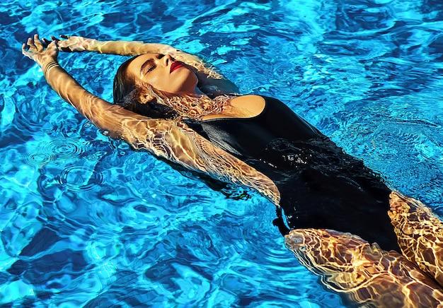 Modèle belle fille aux cheveux noirs en maillot de bain noir