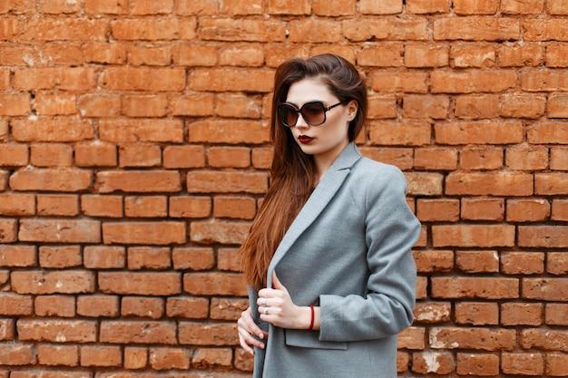 Modèle de belle fille brune dans un manteau gris avec des lunettes de soleil près d'un mur de briques rouges
