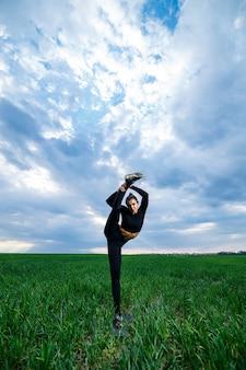 Modèle de belle fille sur l'herbe verte faire du yoga. une belle brune sur une pelouse verte exécute des éléments acrobatiques. gymnaste flexible en noir fait des exercices