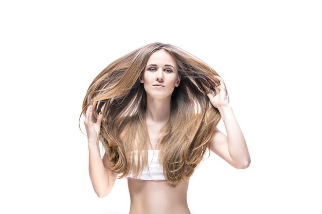 Modèle de belle jeune femme aux longs cheveux blonds et maquillage naturel posant sur blanc