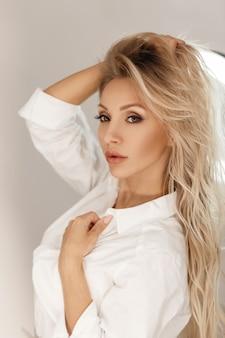 Modèle de belle jeune femme blonde avec maquillage posant près d'un miroir