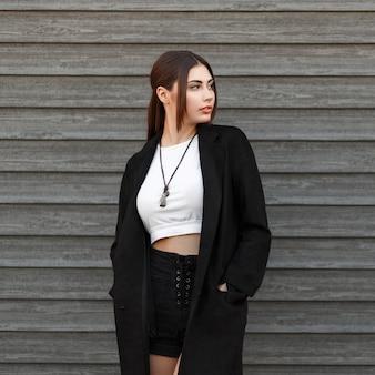 Modèle de belle jeune femme dans un manteau noir se dresse près d'une maison en bois