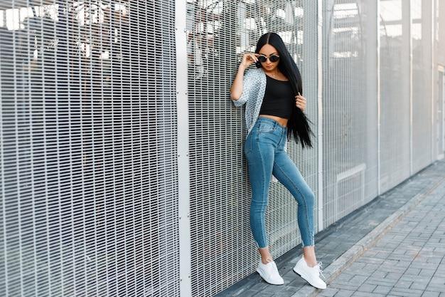Modèle de belle jeune femme avec des lunettes de soleil élégantes dans une cape blanche