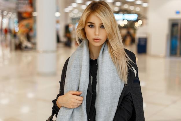 Modèle de belle jeune femme en manteau tendance avec écharpe à l'intérieur
