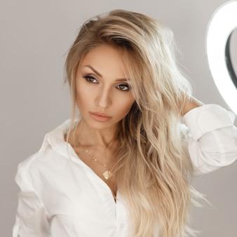 Modèle de belle jeune femme sexy avec du maquillage dans une chemise blanche près du miroir
