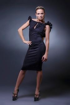 Modèle de belles femmes dans des vêtements et accessoires à la mode tourné isolé sur fond noir dans le studio