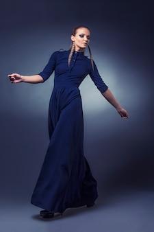 Modèle de belles femmes dans des vêtements et accessoires à la mode tourné isolé sur fond noir