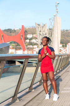 Modèle black afro girl posing souriant et amusant dans la ville au coucher du soleil portant une robe rouge et des baskets blanches et regardant votre smartwatch