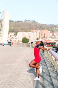 Modèle black afro girl posing souriant et amusant dans la ville au coucher du soleil portant une robe rouge et des baskets blanches