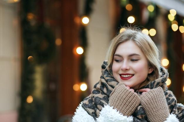 Le modèle blond joyeux porte un manteau d'hiver et une écharpe en tricot marchant dans la ville. espace pour le texte