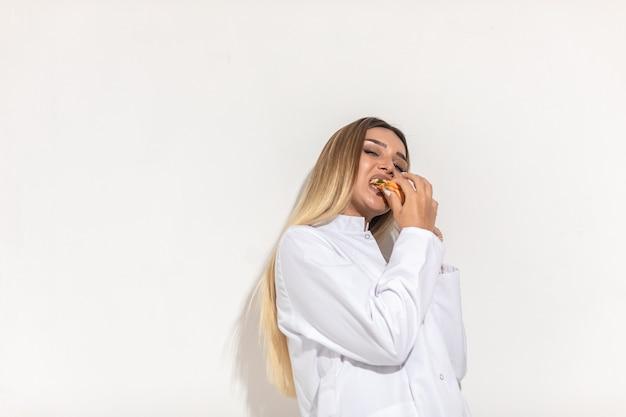Modèle blond mordant un sandwich et appréciant.