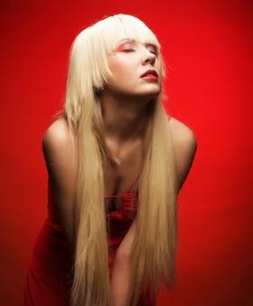 Modèle blond parfait en robe rouge sur fond rouge. maquillage fantaisie.