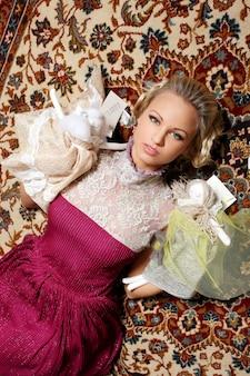 Modèle blond en robe rose avec détail en tulle allongé sur le sol