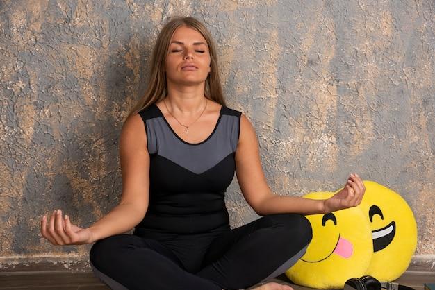 Modèle blonde assis en position du lotus avec un oreiller emoji souriant et la langue dehors.
