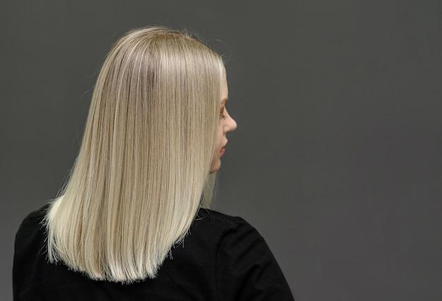 Modèle blonde aux cheveux raides, regarde par derrière. résultat décoloration des cheveux. espace pour le texte