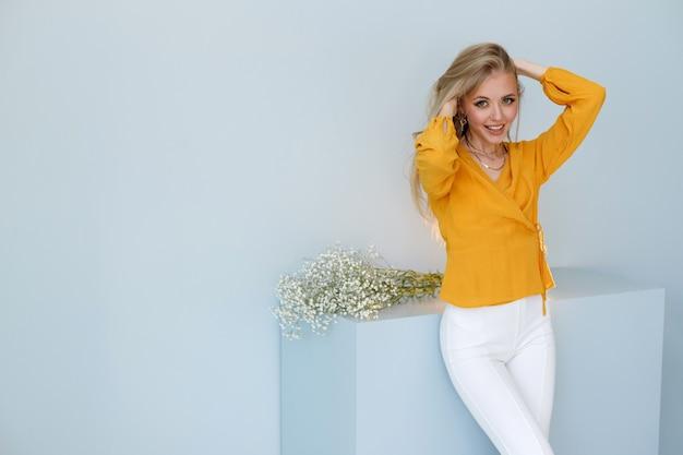 Modèle blonde aux cheveux sains sur fond tendance. esthétique. cosmétologie et soins capillaires