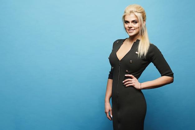 Modèle blonde dans une robe longue avec fermeture éclair devant posant au mur bleu