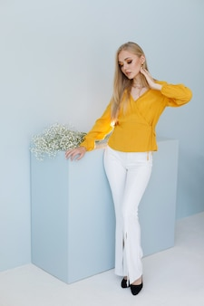 Modèle blonde dans des vêtements élégants sur fond bleu. affiche. achats en ligne