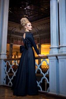 Modèle blonde élégante vêtue d'une robe de princesse avec un noeud dans le dos, regardant de côté